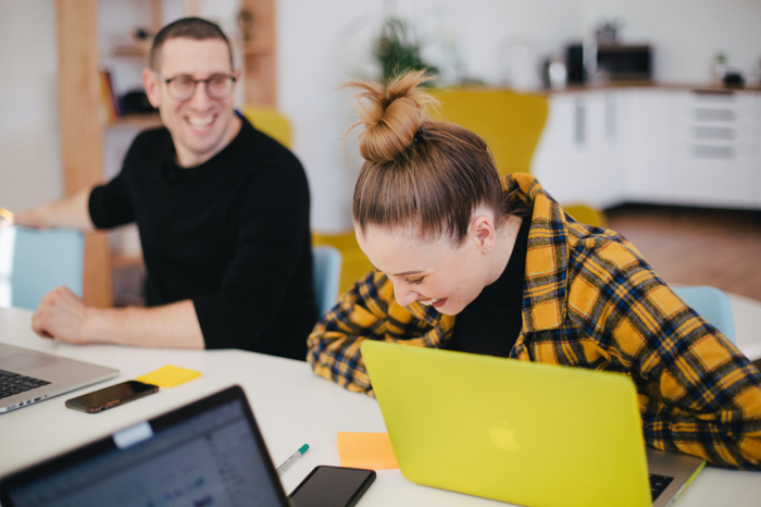 two employees laughing about marketing career path